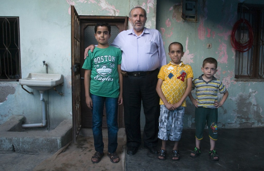 Abdul Abdurrazzak Othman, a retired physics teacher who spent 15 years in prison, he is pictured with his sons
